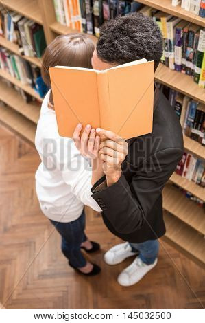 American students kissing in library and hiding behind the book. Students standing between bookshelves in library.