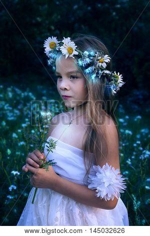 Little beautiful girl with a luminous flower