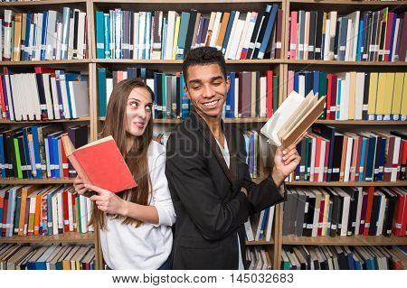 American students reading books in library. People standing back to back and communicating in University library.
