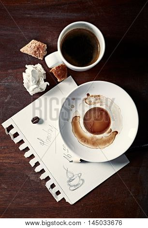 Paper sheet with notice and a cup of coffee on work table; seen from above