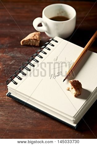Notebook, pencil and a cup of black coffee on work table