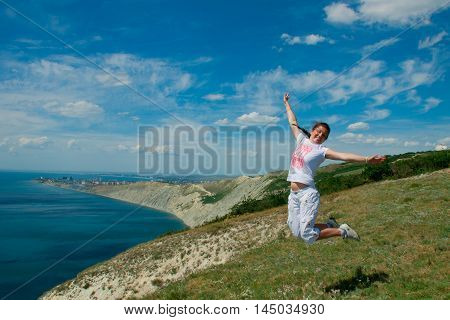 girl jumping on the hill against the sky in summer