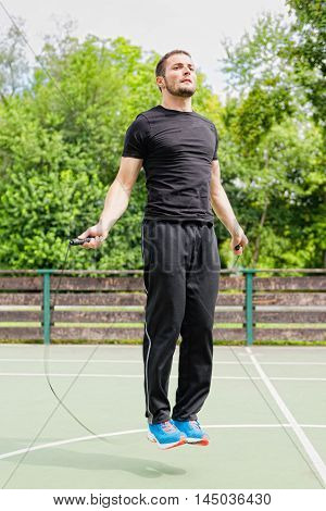 Young male athlete jumping rope outdoors, toned image