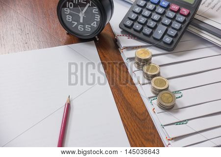 pencil reports arranged and document place with paperclip have calculator clock and Coin on wooden floor.