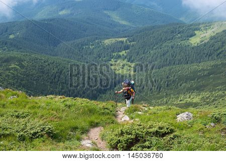 Hiker climbs to the top of the steep slope. The difficult trekking in Carpathian Mountains