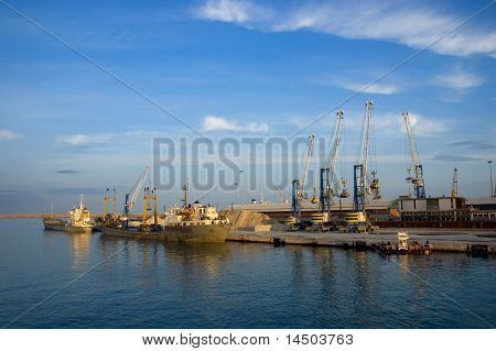 Some ships in the port in the soft and warm light of the sunrise