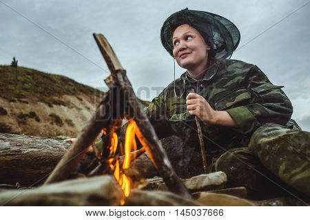 Girl hiker stirs firewood around campfire on river shore at evening.