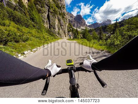 Cyclist on mountainous road in a sunny day. Cycling in Dolomites Passo Falzarego. POV Original point of view