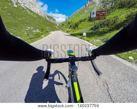 Cyclist on mountainous road in a sunny day. Cycling in Dolomites Passo Falzarego. POV Original point of view.
