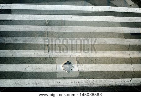 Old pedestrian crosswalk in black and white on city street safety concept.