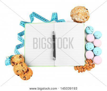 Measuring tape, bakery products and notepad on white background