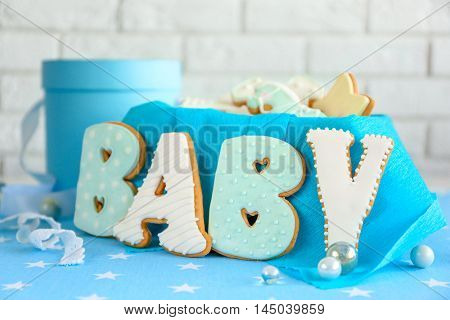 Baby glazed cookies in box on decorated table