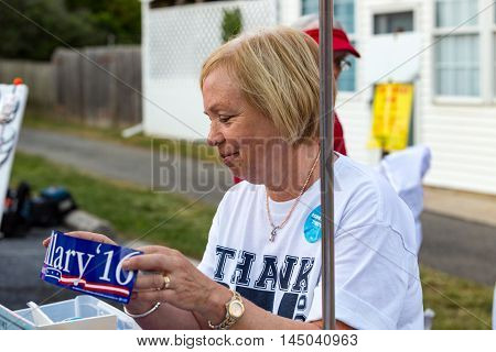 Lancaster PA - August 30 2016: A woman selling a Hillary Clinton bumper sticker at a rally for Virginia Senator Tim Kaine.