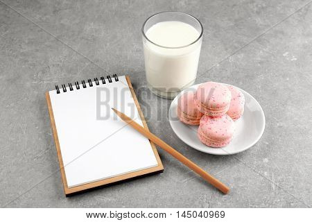 Notepad,milk and cookie on color background