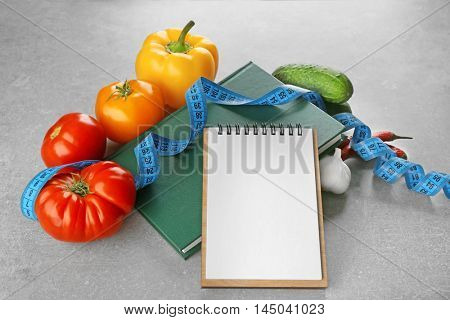 Vegetables, measuring tape and notepad on color background