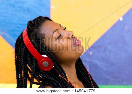 Cheerful african woman dancing and listening music