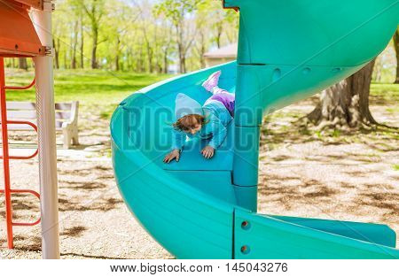 Little girl on the playground having fun Little girl playing in the park on a swing