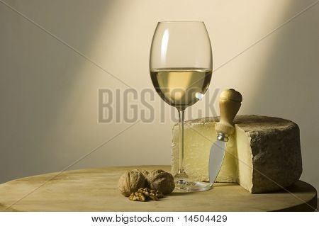 Cutting board with genuine Italian food. White wine glass, ripe hard cheese from ewe's milk and walnuts. Warm ray of light in the background. Space for text