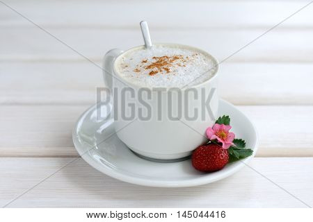 frothy coffee with cinnamon and with decoration of berry flower and leaf strawberries / coffee with the aroma of cinnamon and strawberry