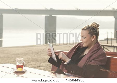 Young attractive woman sitting in an outdoor cafe by the river drinking tea holding a tablet computer and surfing the net on a sunny autumn day
