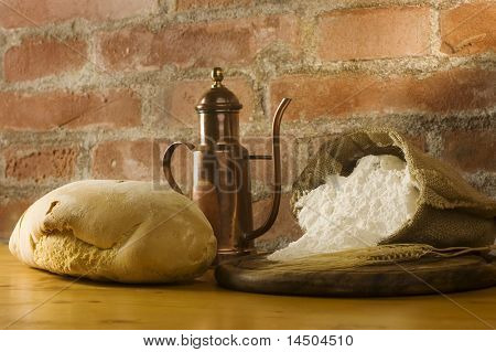 Rural kitchen with loaf of bread, wheat ears, oil and a sack of white flour