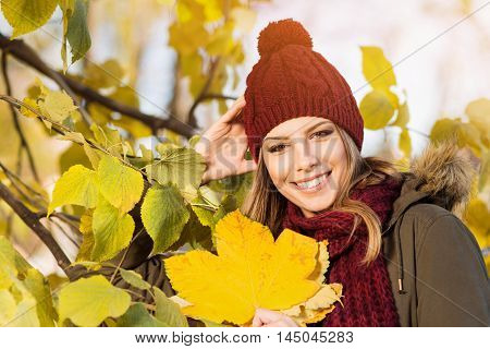Beautiful young woman in knitted dark red beanie hat with pompom and scarf outdoors in park in autumn, smiling, standing by the tree with yellow leaves. Vibrant colors, natural light, medium retouch.