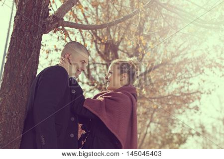 Young couple in love standing next to a tree on an autumn vacation enjoying the nature hugging