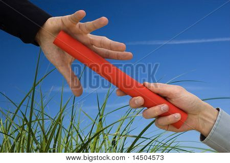 One businessman passing a red baton to another businessman over a green meadow. Symbol of teamwork, helping and partnership with an eye for the environment.