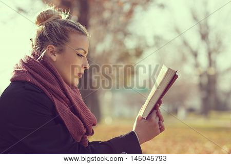 Beautiful young blond leaning on a tree on an autumn day reading a book