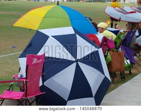 Dallas, USA, 13th August 2016. Umbrella laden soccer spectators watch games at 19-field Money Gram Soccer Park owned by City of Dallas, 13th Augsut, 2016 in Dallas,