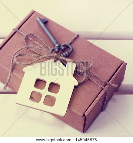background with a box corded and the key symbol of the house / symbolic gift with the idea of home