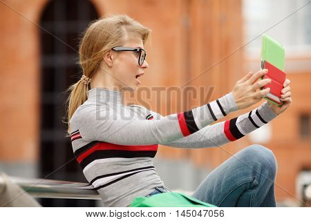 girl in glasses making photo using tablet computer