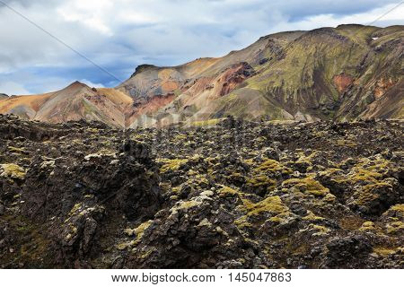 National Park Landmannalaugar in Iceland. Pieces of gray and black lava, sometimes covered with green moss. In the background - pink and orange rhyolite mountains