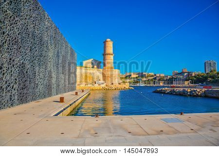 The warm sunny day in the Mediterranean. Scenic Fort St. John is reflected in the blue water port