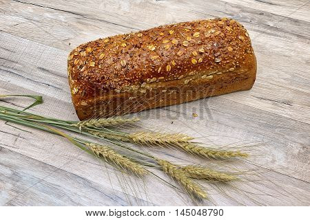 loaf of rye bread and ears of wheat on the wooden background. horizontal photo.