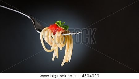 Spaghetti pasta with tomato and basil on fork. Fine Italian food. Space for text. Professional studio image