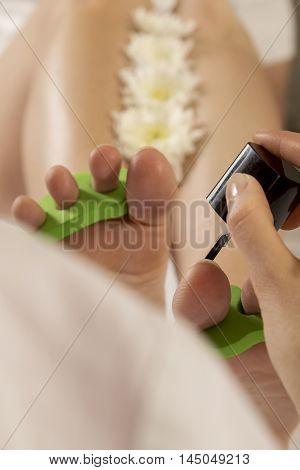 Woman's feet in pedicure toe separators at the nail salon. Beautician applying nail polish