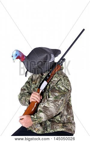 A Hunter dressed in camouflage holds his shot gun and wears a Turkey Decoy on his head. Isolated on white with room for your text.