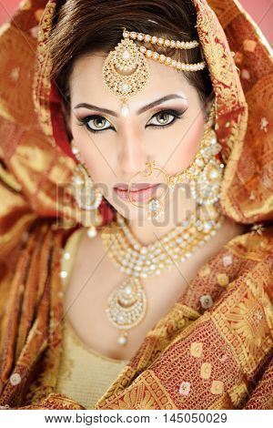 Portrait of a pretty girl in traditional Indian Pakistani bridalwear with heavy jewelry and makeup