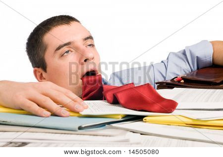 Young exhausted businessman with his necktie like a stuck out tongue lying down heap of documents.