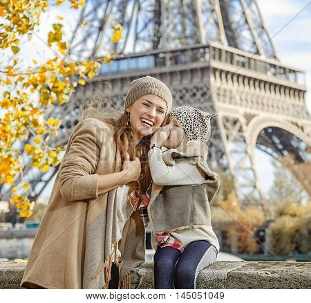 Daughter Whispering Something To Mother Near Eiffel Tower