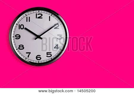 Smiling clock on vivid pink wall reads ten past ten with copy space