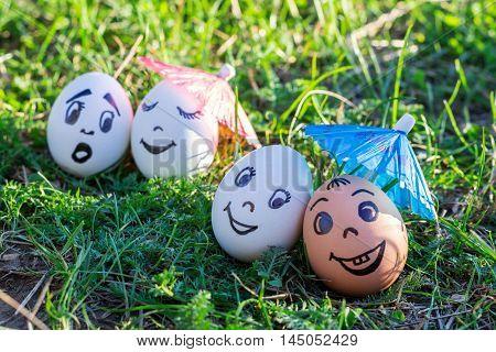 Funny eggs under umbrellas imitating happy mixed couple and indignant white couple