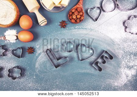 Heart - shaped cookie cutters, flour and word Love, made with it, and other stuff for baking cookies, lying on blue background.