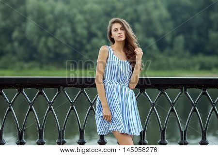 Portrait young beautiful woman in white blue striped dress summer river park outdoors