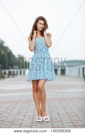 Spring Beautiful Woman In Summer Dress Walking In City River Park Enjoying Weekend. Playful And Beau