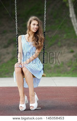 Beautiful Young Woman In White Blue Striped Dress Having Fun On A Swing In City Park