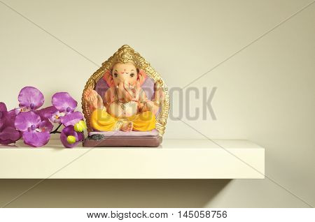 Small handcrafted colorful idol of Lord Ganesha placed on a white shelf. Most worshiped Deity in India.