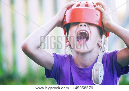 Boy in hockey helmet outdoors. boy shouting head thrown back. the concept of a fan support the hockey team