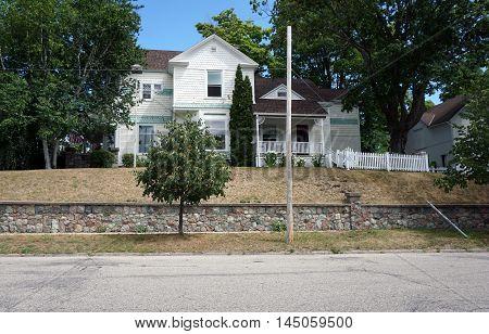 PETOSKEY, MICHIGAN / UNITED STATES - AUGUST 5, 2016: A yellow home on a hill near downtown Petoskey, Michigan.